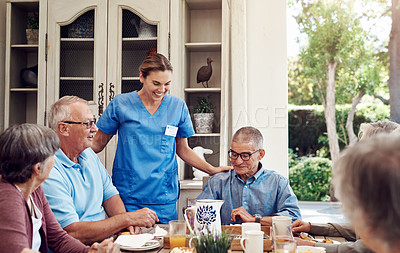 Buy stock photo Cropped shot of an attractive young nurse bonding with her senior patients during a tea party