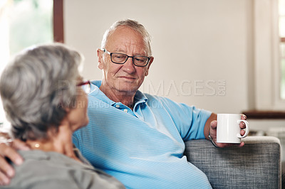 Buy stock photo Shot of a senior couple enjoying a coffee break while relaxing together on the sofa at home