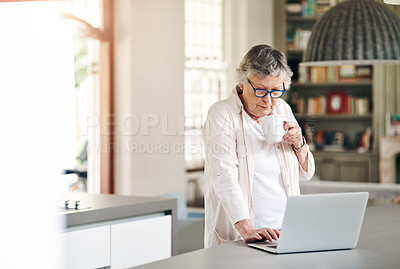 Buy stock photo Shot of a senior woman having coffee while using a laptop at home