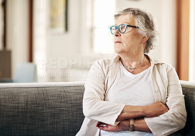 Buy stock photo Shot of a senior woman sitting on the sofa at home and looking thoughtful