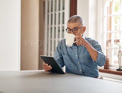 Buy stock photo Shot of a senior man having coffee and using a digital tablet at home