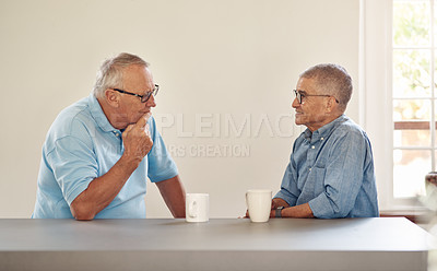 Buy stock photo Shot of two senior men having coffee and a chat at home