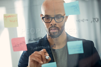 Buy stock photo Cropped shot of a young businessman brainstorming with notes on a glass wall in an office