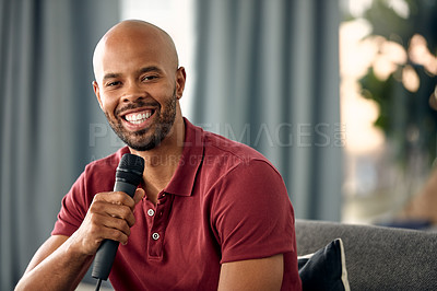 Buy stock photo Cropped shot of a young man sitting on a sofa while speaking over a microphone