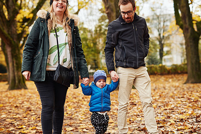 Buy stock photo Cropped shot of an affectionate young couple walking through a park with their little son in autumn