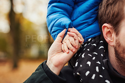 Buy stock photo Cropped shot of an unrecognizable father carrying his little son on his shoulders in a park in autumn