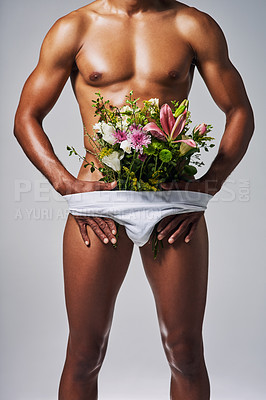 Buy stock photo Cropped shot of an unrecognizable man posing with a bouquet of flowers stuffed in his underwear against a grey background