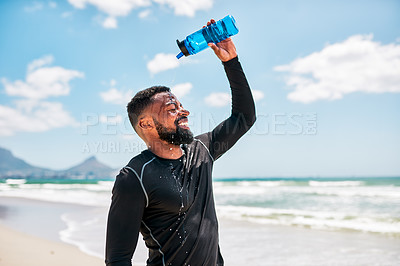 Buy stock photo Cropped shot of a carefree young man pouring water over himself to cool off after training exercises outside on a beach during the day
