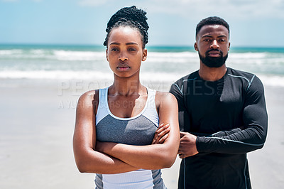 Buy stock photo Portrait of a confident young couple standing together with their arms folded on a beach outside during the day