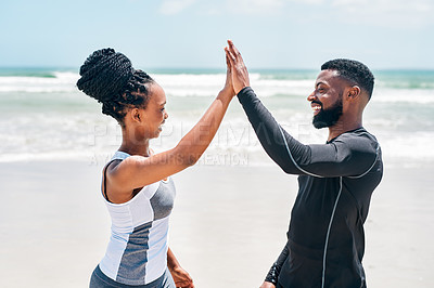 Buy stock photo Cropped shot of a cheerful young couple giving each other a high five while standing together on a beach  outside during the day