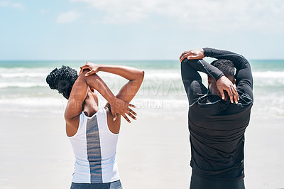 Buy stock photo Rearview shot of a cheerful young couple doing stretching exercises together on a beach outside during the day