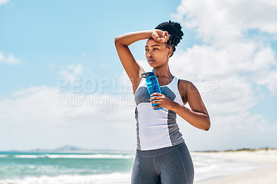 Buy stock photo Cropped shot of a confident young woman holding her water bottle while looking into the distance outside on a beach during the day