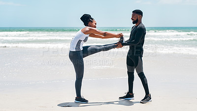 Buy stock photo Shot of a cheerful young couple helping each other out with stretching exercises outside on a beach during the day
