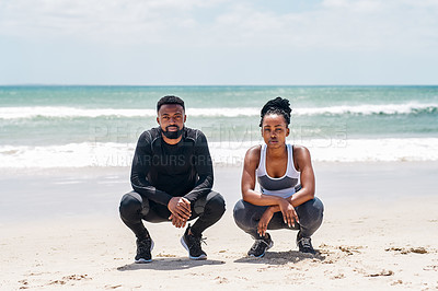 Buy stock photo Portrait of a confident young couple standing together on a beach before starting with training exercises outside during the day