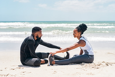 Buy stock photo Shot of a confident young couple doing stretching exercises together outside on a beach during the day