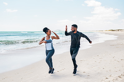 Buy stock photo Shot of a cheerful young couple having a jog together while giving each other a high five outside on the beach