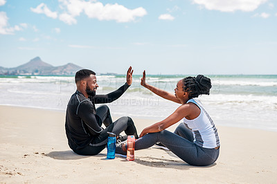 Buy stock photo Shot of a cheerful young couple doing stretch exercises and giving each other a high five while being seated on a beach outside during the day
