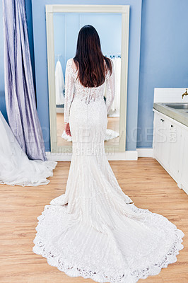 Buy stock photo Rearview shot of an unrecognizable bride looking at herself in the mirror while fitting her wedding gown in a bridal shop