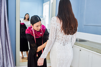 Buy stock photo Cropped shot of an attractive young bridal shop assistant helping a customer with fitting her wedding gown