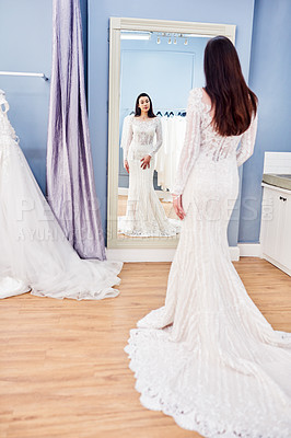 Buy stock photo Full length shot of a beautiful young bride looking at herself in the mirror while fitting her wedding gown in a bridal shop