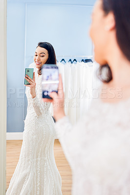 Buy stock photo Cropped shot of a beautiful young bride taking a selfie while standing in front of a mirror in a bridal shop