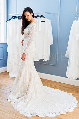 Buy stock photo Full length shot of a beautiful young bride fitting her wedding gown in a bridal shop