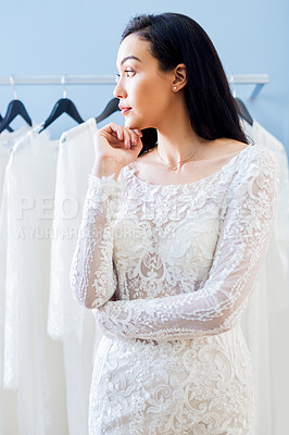 Buy stock photo Cropped shot of a beautiful young bride looking thoughtful while fitting her wedding gown in a bridal shop