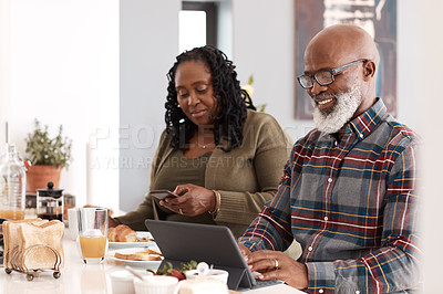 Buy stock photo Shot of a mature couple using their digital devices while having breakfast together at home