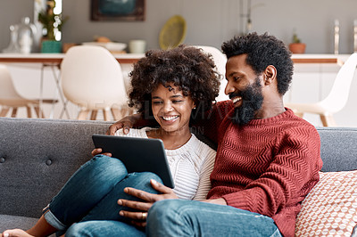Buy stock photo Shot of an affectionate couple using a digital tablet while relaxing on the sofa at home
