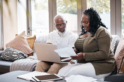Buy stock photo Shot of a mature couple using a laptop while going through paperwork together at home