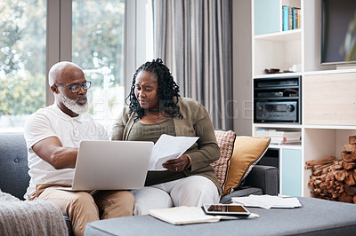 Buy stock photo Shot of a mature couple looking stressed out while going through paperwork together at home