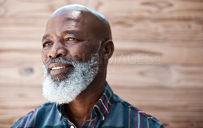 Buy stock photo Shot of a mature man looking thoughtful while standing against a brown background
