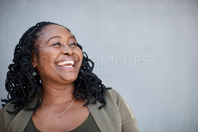 Buy stock photo Shot of a mature woman looking thoughtful while standing against a grey background