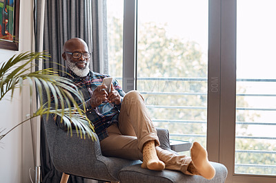 Buy stock photo Shot of a mature man using a cellphone while relaxing on a sofa at home