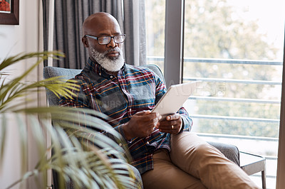 Buy stock photo Shot of a mature man using a digital tablet at home