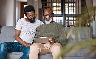 Buy stock photo Shot of a happy senior man using a digital tablet while spending some time with his adult son at home