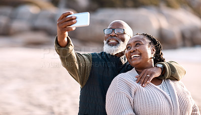 Buy stock photo Shot of a happy mature couple taking selfies with a smartphone at the beach