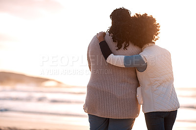 Buy stock photo Rearview shot of a young woman embracing her mother while watching the sunset at the beach