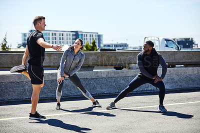 Buy stock photo Shot of a fitness group stretching before their run
