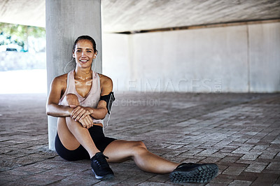 Buy stock photo Full length portrait of an attractive young female athlete taking a rest while working out in the city