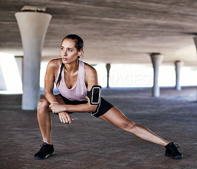 Buy stock photo Full length shot of an attractive young female athlete stretching during her workout in the city