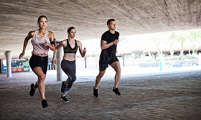 Buy stock photo Full length shot of three young athletes working out in the city