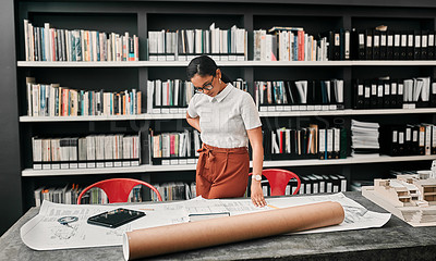 Buy stock photo Cropped shot of an attractive young female architect working with blueprints in a modern office