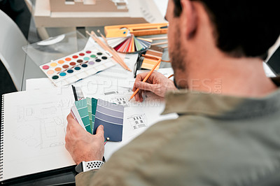 Buy stock photo Cropped shot of an unrecognizable male architect working with some blueprints in a modern office
