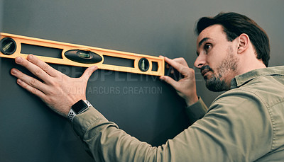 Buy stock photo Cropped shot of a young architect holding a spirit-level against a wall