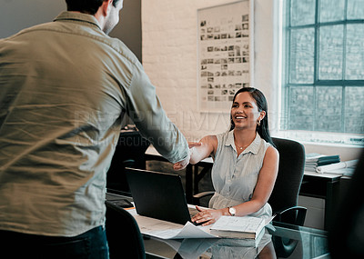 Buy stock photo Cropped shot of two young businesspeople shaking hands in an office
