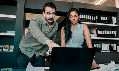 Buy stock photo Shot of two young businesspeople discussing something on a laptop