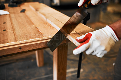 Buy stock photo Cropped shot of an unrecognizable carpenter cutting wood inside a workshop