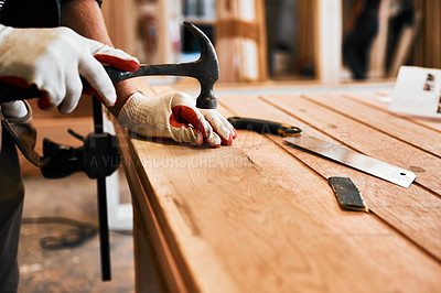 Buy stock photo Cropped shot of an unrecognizable carpenter hammering nails on wood inside a workshop