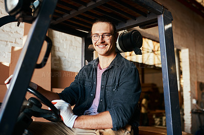 Buy stock photo Shot of a young male warehouse worker driving a forklift